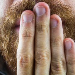 man with beard holding hand up to mouth