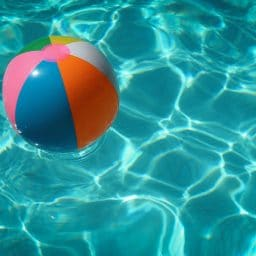 A colorful beach ball floats in a pool.