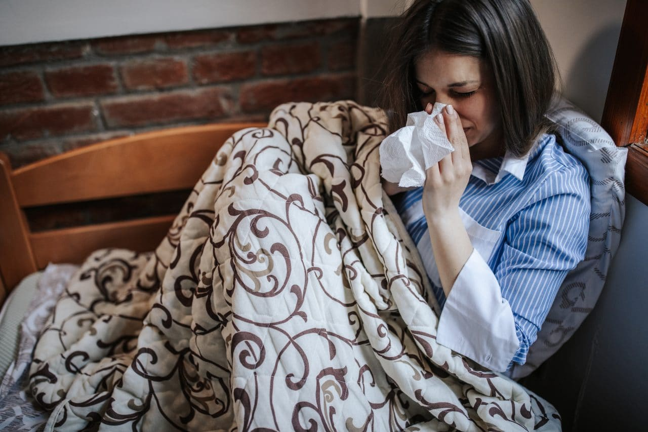 Young sick woman,Infected with a virus, sitting in bed and blowing nose