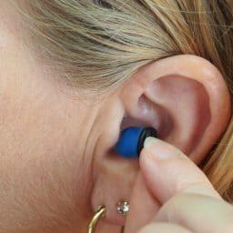 Woman putting on earplugs.